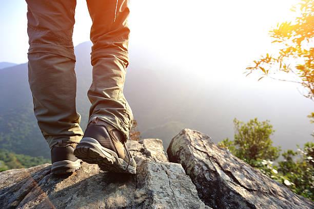 hiking feet mountain peak rock stock photo