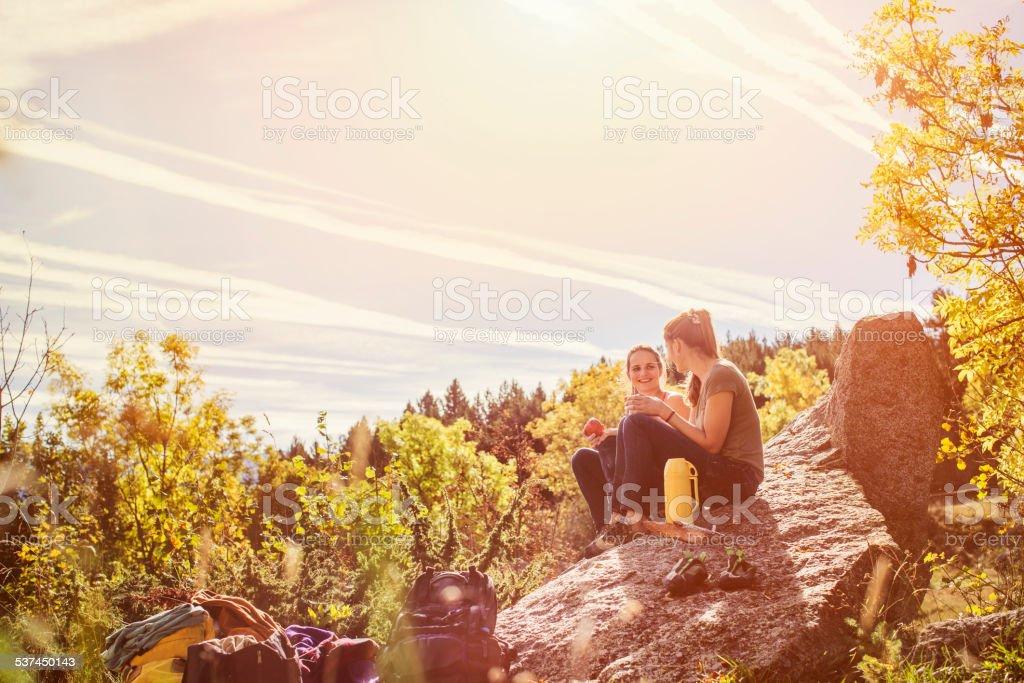 Hiking female friends having snacks on rock stock photo