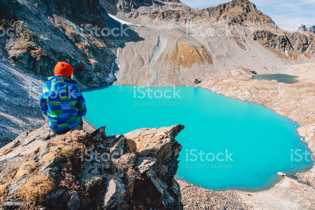 Hiking girl looks at the lake from a height. Beautiful turquoise lake in the mountains. stock photo