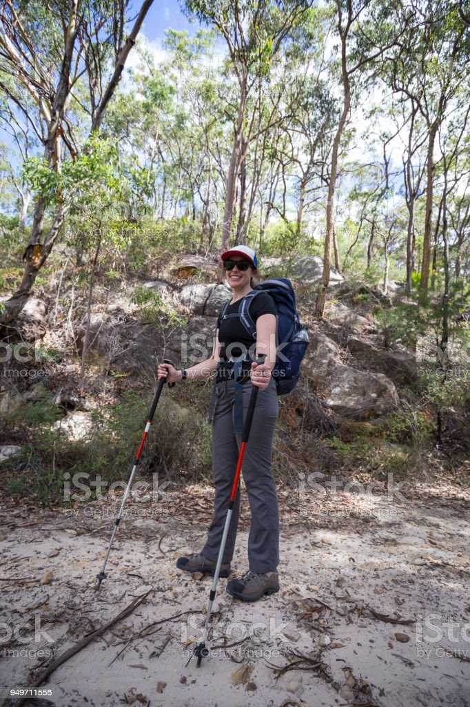 A hiking girl stops for a break during a hot day hiking stock photo