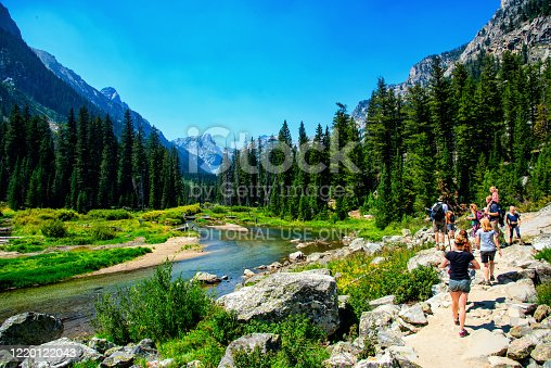 Jackson, United States - August 15, 2018:  A group hiking along a trail near the Moran Creek in Grand Teton National Park, Wyoming, United States.