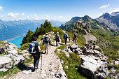 Schynige Platte, Canton of Bern, Switzerland - July 1, 2018 : On the top of the Schynigen Platte. A group of hikers on the ridge above Lake Brienz, Bernese Oberland, Switzerland.