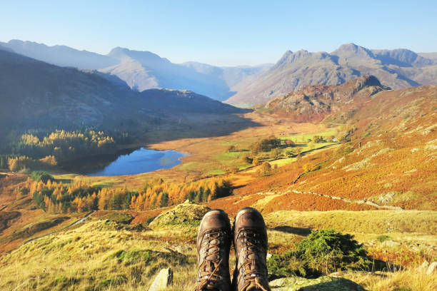 Hiking in autumn with a beautiful natural landscape view A hiker admiring the view of an autumn natural landscape after a walk in the mountains english lake district stock pictures, royalty-free photos & images