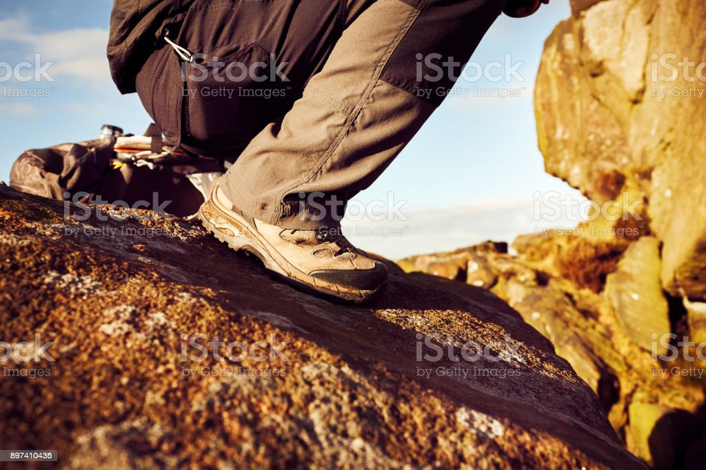 Close up of feet of male hiker walking over rocks on mountain. Hiking...