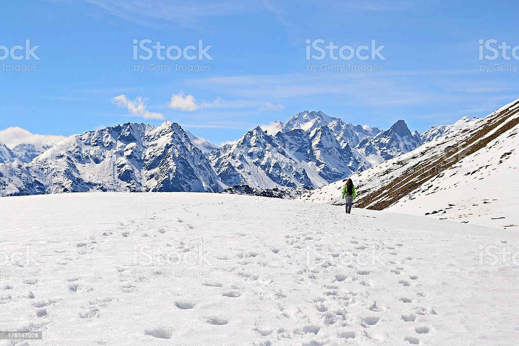 Hiking in the Alps Alpinist with backpack walking on snowy ridge while looking at the majestic high mountain range (over 4000 m) in Gran Paradiso National Park, in spring season. Active Lifestyle Stock Photo