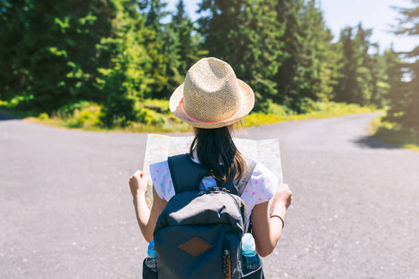 Hiking little girl traveler with backpack checks map to find directions in wilderness area, real explorer stock photo