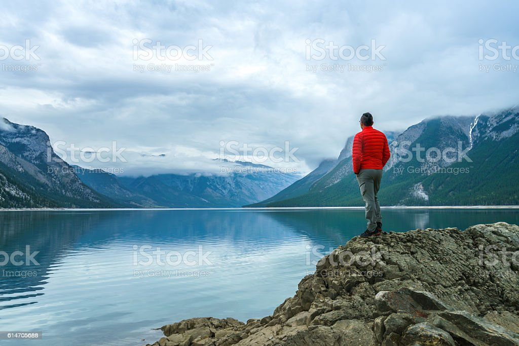 Hiking man arms open to nature view stock photo