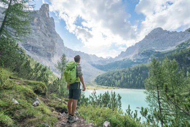 Hiking man contemplating Alpine lake in Italy stock photo