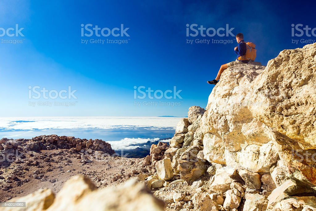 Hiking man or trail runner looking at view in mountains stock photo