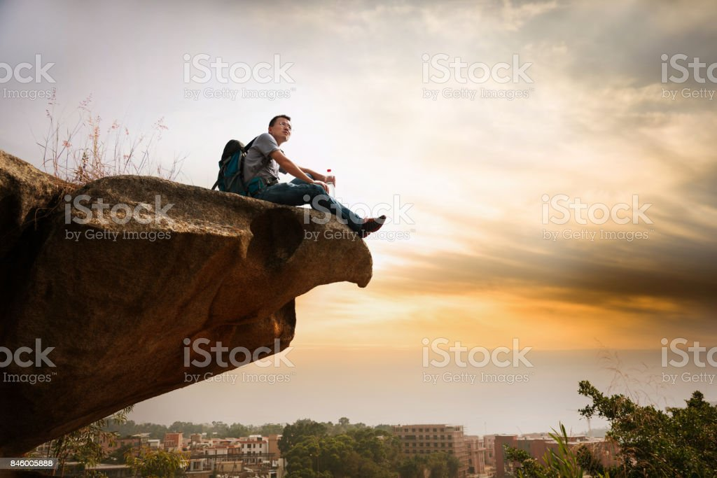 Mann sitzt auf dem Felsen wandern Lizenzfreies stock-foto