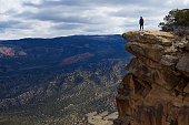 A woman stands near the edge of a cliff while hiking a popular trail near Moab, Utah, USA. She is wearing a backpack.