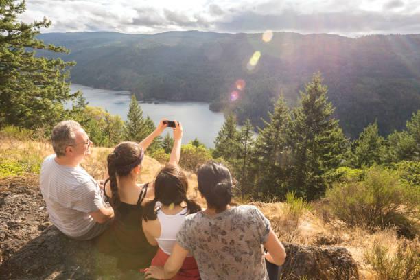 ハイキング、多民族の家族の携帯電話で山の頂上に selfie を取って - カナダ旅行 ストックフォトと画像