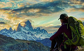 Female hiker rests and watches dramatic sky over Mount Fitzroy