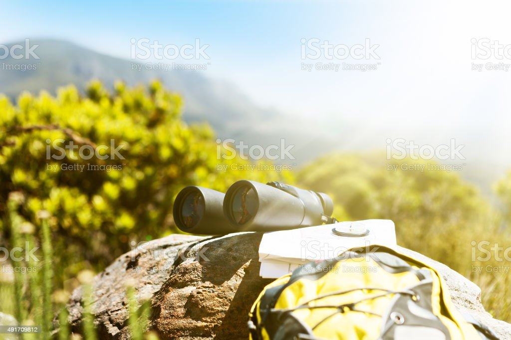 Hiking necessities on rock: binoculars, map, compass, and backpack stock photo