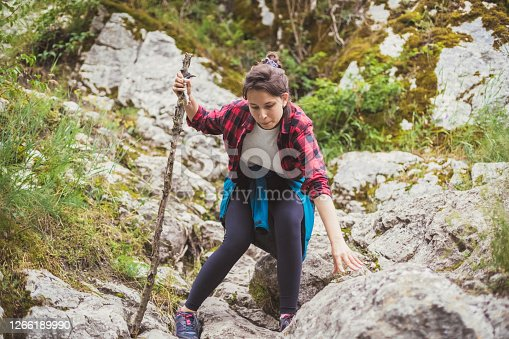 View of a young woman overcoming steep and rough parts of unmarked paths during her hiking weekend. Luckily, she's found a stick nearby to help her out.