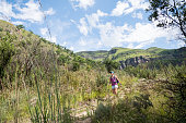 A mid adult female hikes along a footbath in the Drakensberg Mountains.