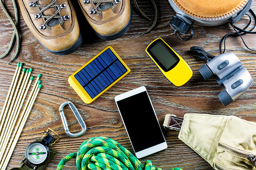 istock Hiking or travel equipment with boots, compass, binoculars, matches on wooden background. Active lifestyle concept. 931339202