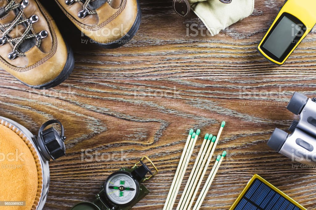Hiking or travel equipment with boots, compass, binoculars, matches on wooden background. Active lifestyle concept zbiór zdjęć royalty-free