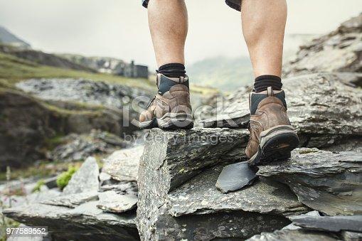 Hiker hiking over rocks on a mountain trail