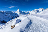 istock Hiking path in front of the Matterhorn in the morning light in winter 1295362511