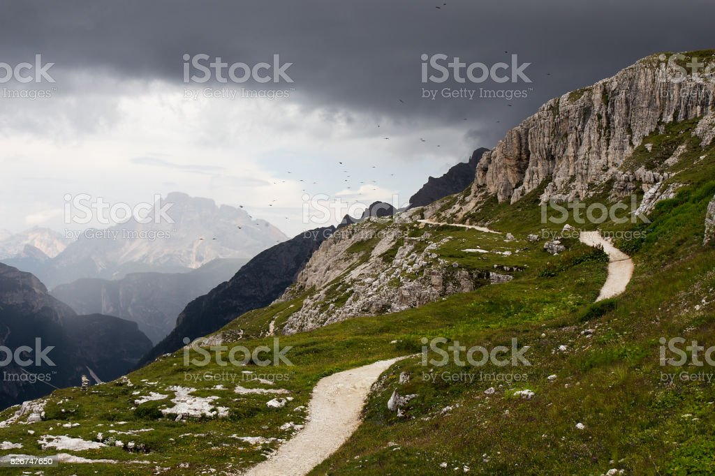 Hiking path in Italian Dolomites with dramatic Sky before the storm stock photo
