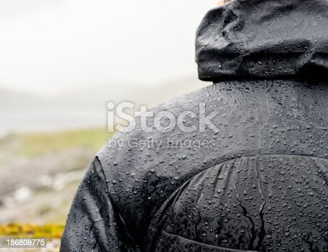 A warm, waterproof jacket protecting a man from heavy rain on a hiking trip.