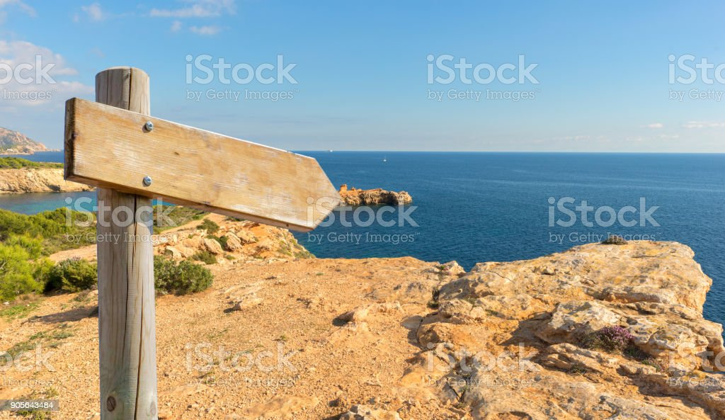 Hiking sign on the mountain by the sea stock photo