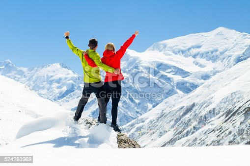 Hiking climbing woman and man, younf couple success in mountains. Fitness and healthy lifestyle outdoors in winter nature.