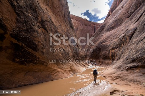A group of hikers treks through the Halls Creek narrows in Capitol Reef National Park.