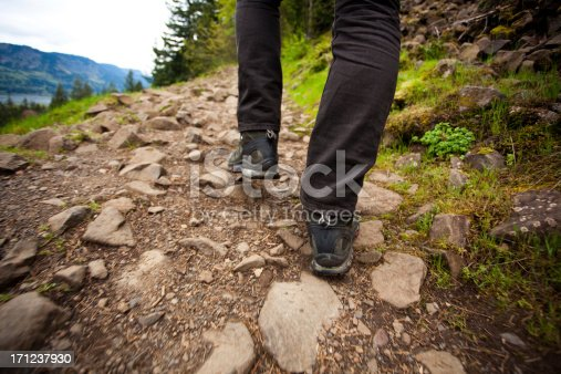 Unrecognizable hikers feet on a rocky forest trail.