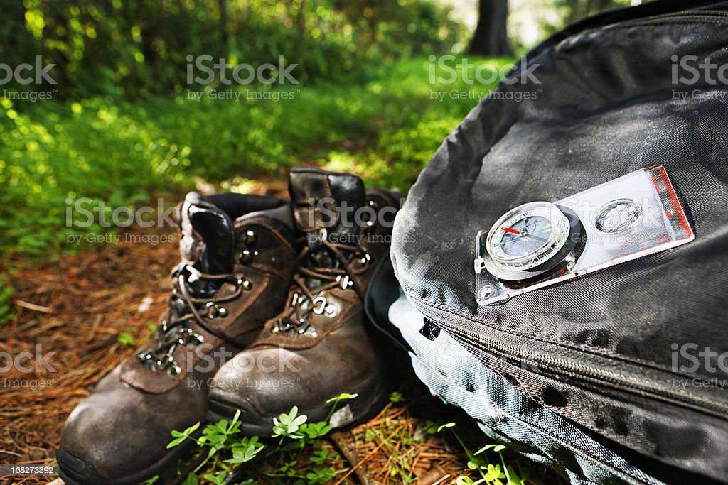 Hiking theme: boots, backpack and compass on sunlit forest path stock photo