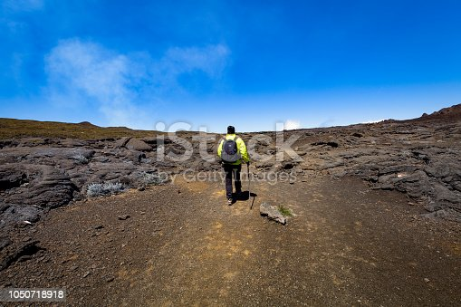 woman hiking through the lava fields of piton de la fournaise volcano at reunion island, french overseas territory, mascarene islands.