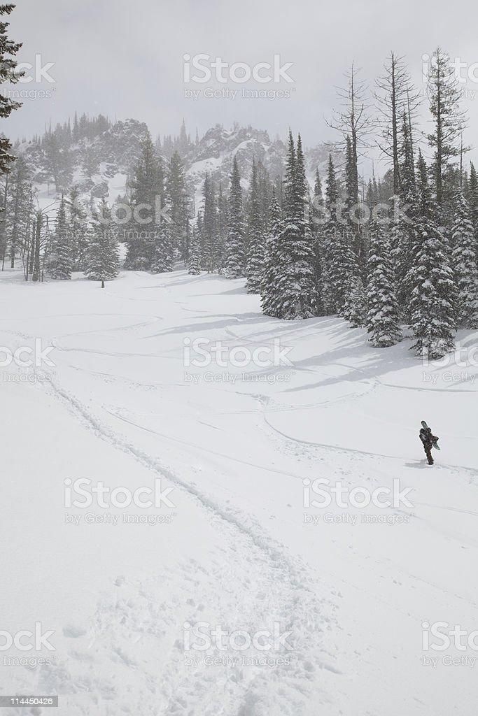 Hiking to the cliffs for extreme snowboarding stock photo