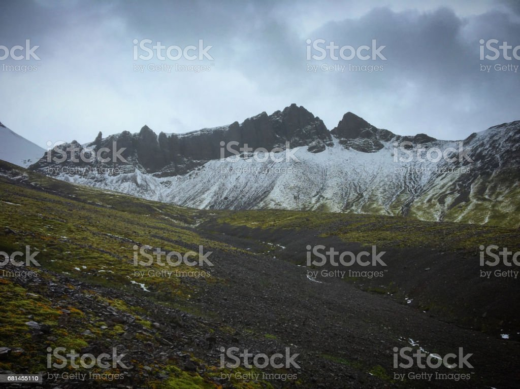 Hiking to the glacier. Tough, cold and wet weather. Wind, a lot of rain. View over mountain range. View to the glacier with ice and snow. Water drops on the lense. royalty-free stock photo