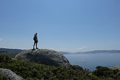 Hiking a rock with a sea and islands background