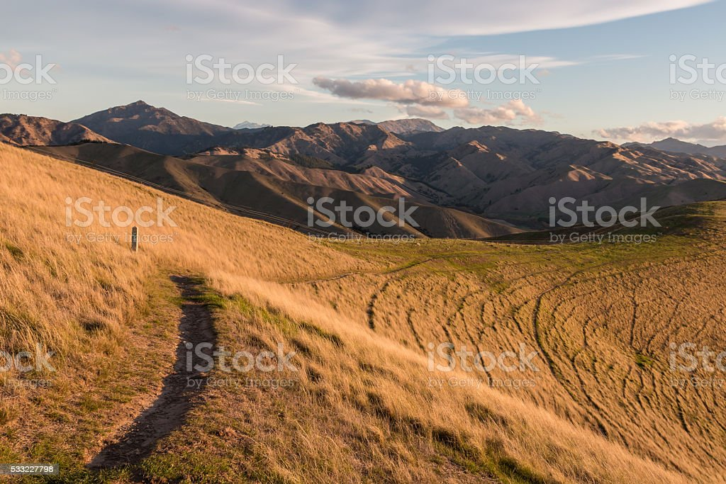hiking track across grassy slopes stock photo