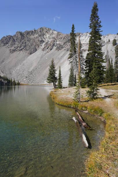 A hiking trail along a calm mountain lake. stock photo