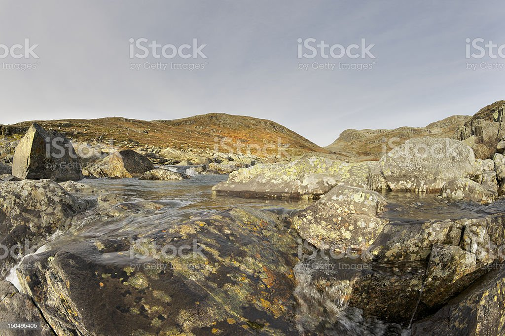 Hiking trail crosses small river in autumn colored mountains royalty-free stock photo