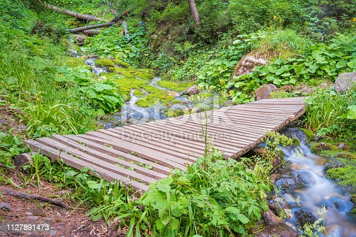 Stock photograph of scenic creek landscape with footbridge in the landmark Ceahlau Massif, Carpathian Mountain Range, Romania.