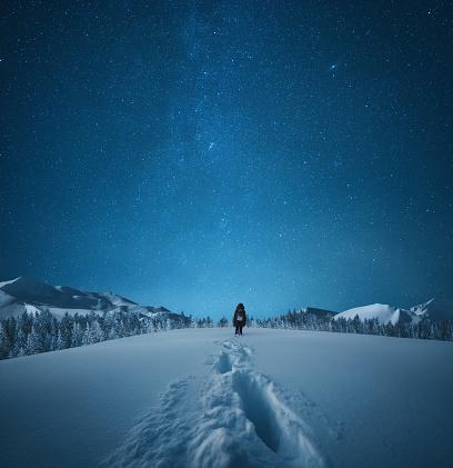 Woman walking in knee-deep snow under the starry night sky.