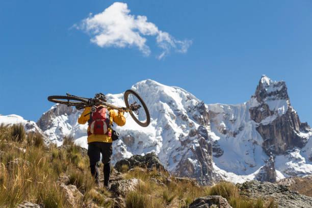Wandern mit Mountainbike auf Schultern in Cordillera Huayhuash, Peru. – Foto