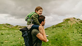 Photo of a little boy, tired from hiking, being held on shoulders by his father // wide photo dimensions