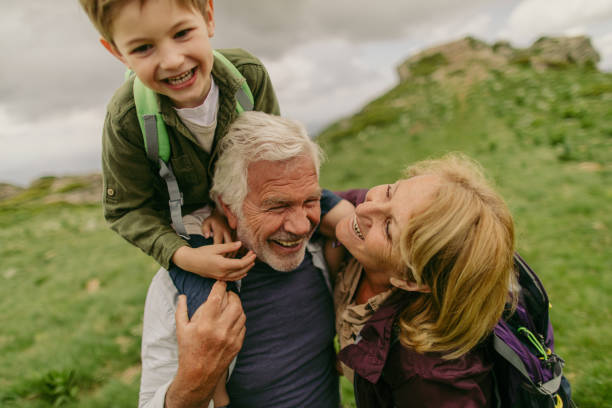 Hiking with my grandparents Photo of a cheerful little boy, who is tired from hiking, being held on shoulders by his grandfather grandson stock pictures, royalty-free photos & images