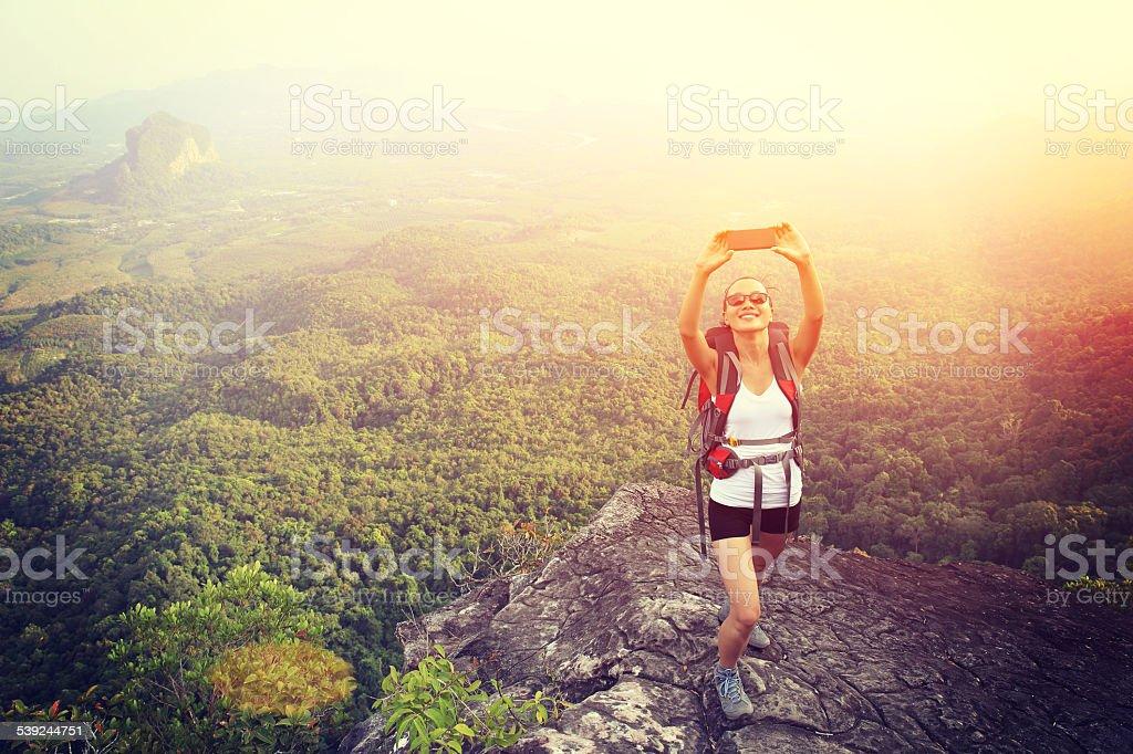 hiking woman taking photo with smart phone on mountain peak royalty-free stock photo