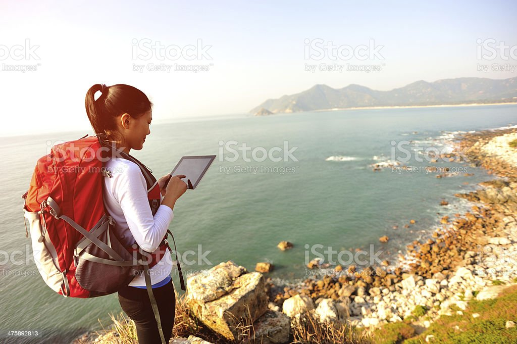 hiking woman use tablet pc seaside stock photo