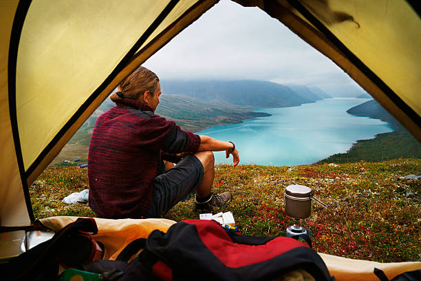 hiking young man and scenic view of lake gjende jotunheimen - tent stock photos and pictures