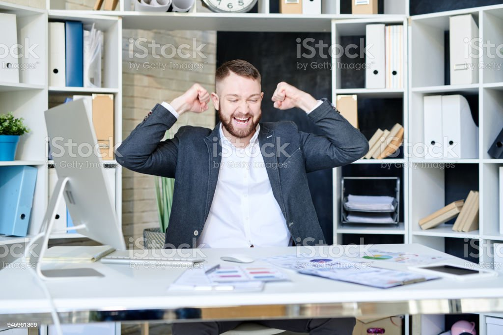 Happy ecstatic bearded young businessman celebrating success and...