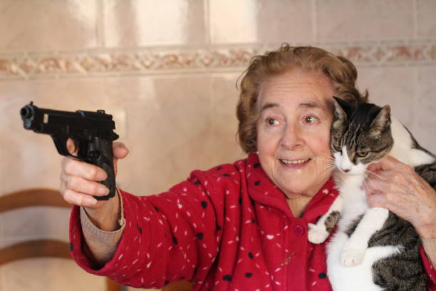 hilarische dame die haar kat beschermt - gun shooting stockfoto's en -beelden