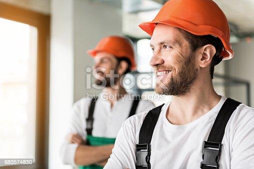 istock Hilarious smiling erectors in room 683574830
