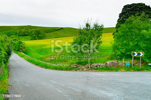 A hill near Chesterfield, Derbyshire with dry stone walls and a road curving through it.